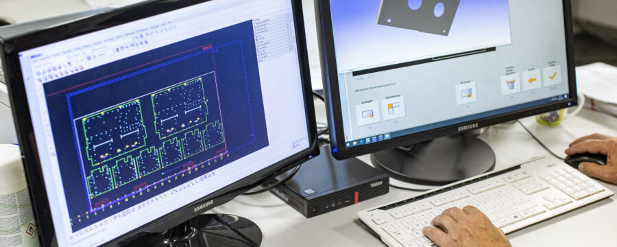 Employee sits in front of two monitors on which CAD designs can be seen